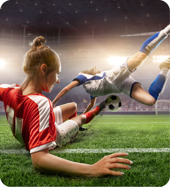 Two female soccer players diving for a ball