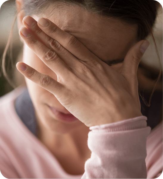 Woman with migraine covering face