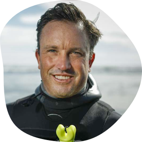 Shawn Dollar in Wet Suit with Ocean in Background