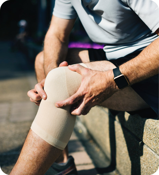 Man in a knee brace with his hands on his knee